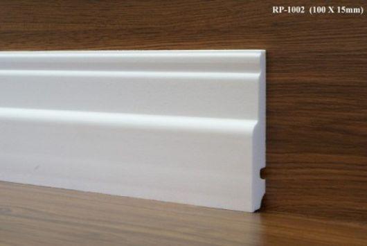 Rodapé de EVA branco, parede e piso de madeira.
