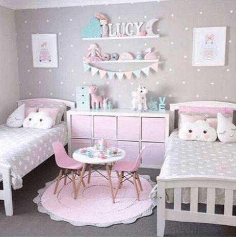 tapete rosa redondo entre duas camas de quarto de crianças
