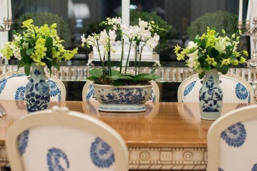 Vasos com flores, no centro da mesa.