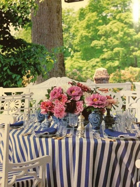 Mesa em espaço externo com louças azuis e vasos.