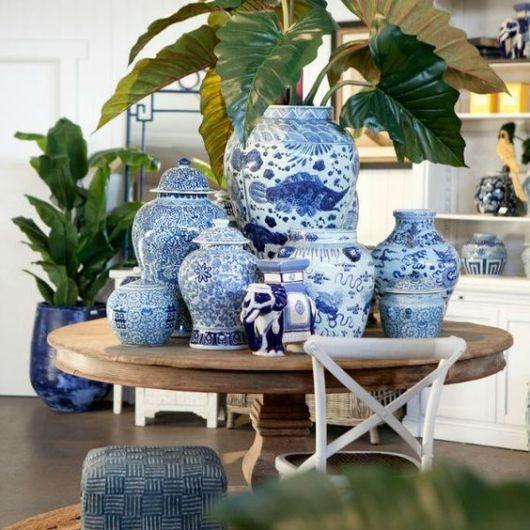 Mesa de madeira com vários vasos azuis e brancos.
