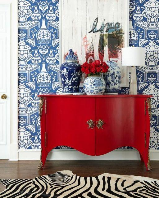 Parede azul, móvel vermelho e vasos brancos e azuis.