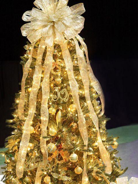 árvore de natal dourada decorada com fitas e laço