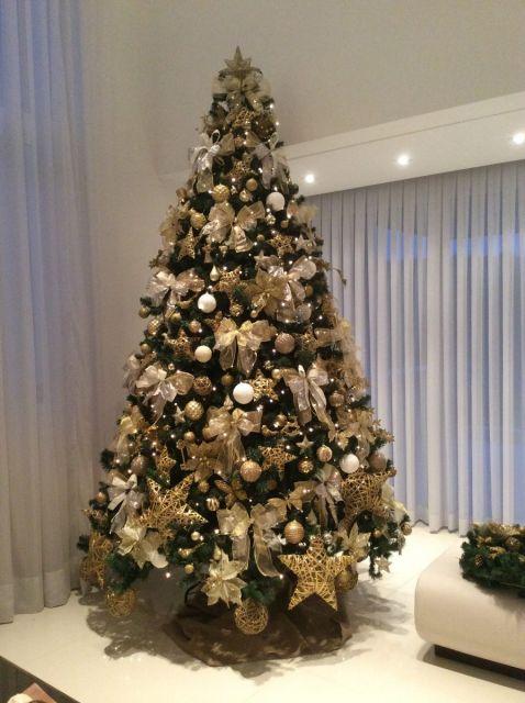 árvore de natal dourada na sala com sofá