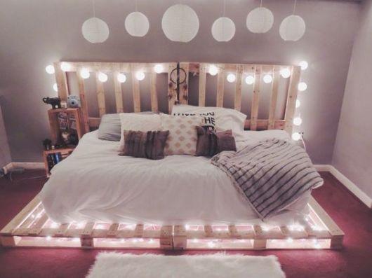 Quaro com roupa de cama clara e luzes na cabeceira e embaixo dos paletes.