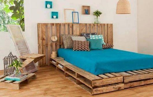 Quarto com paredes brancas, cama e piso de madeira.