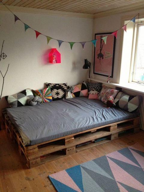 Cama de paletes com futon em cima e várias almofadas.