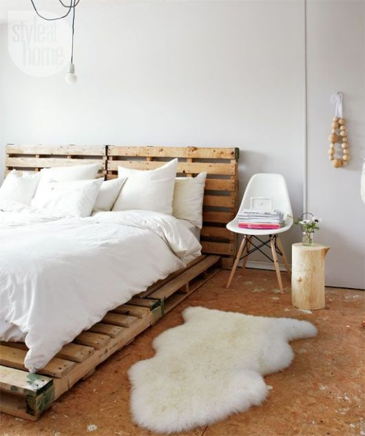 Quarto com decoração branca, com móveis e piso de madeira.