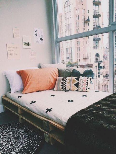 Cama de paletes de solteiro próxima de janela.