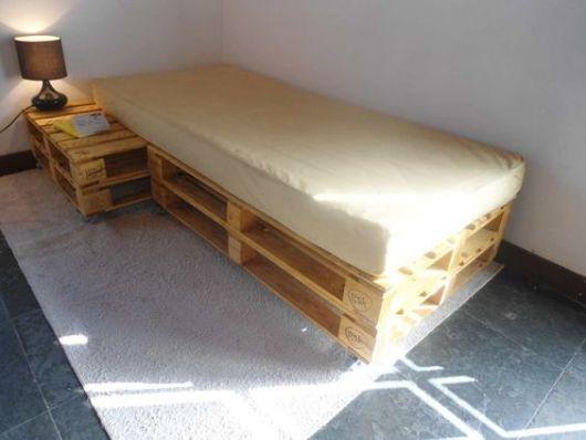 Quarto sem decoração com cama de paletes e colchão.