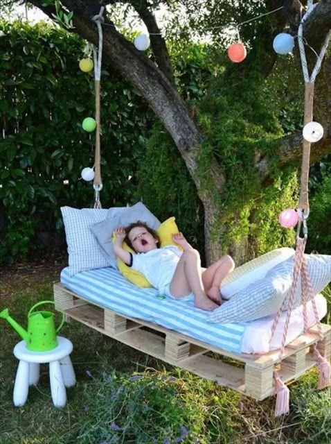 Criança deitada sobre balanço feito de palete.