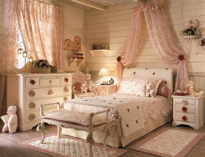 Quarto feminino em tons pastéis com cortinas de renda rosê.