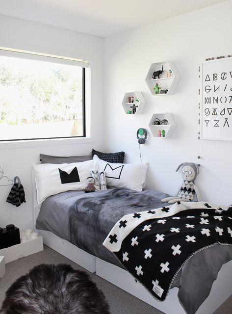 Modelo de quarto feminino nas cores preto e branco com colcha decorada de estrelas e almofadas de gatos.