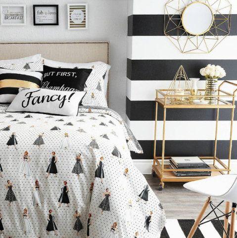 Quarto feminino preto e branco com listras na parede nessas cores.