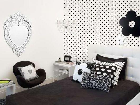 Modelo de quarto feminino preto e branco com almofadas divertidas.