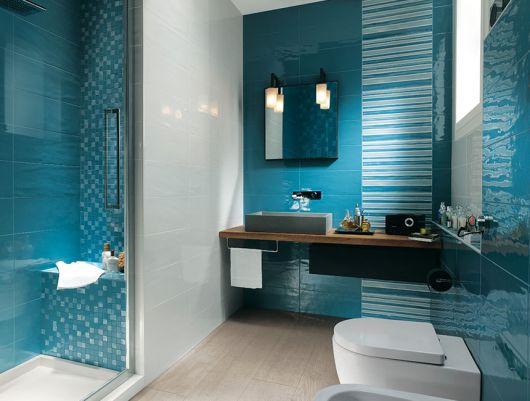 Banheiro pequeno na cor azul escuro com detalhes de adesivos nas cores azul claro nas paredes e pia em madeira na cor marrom.