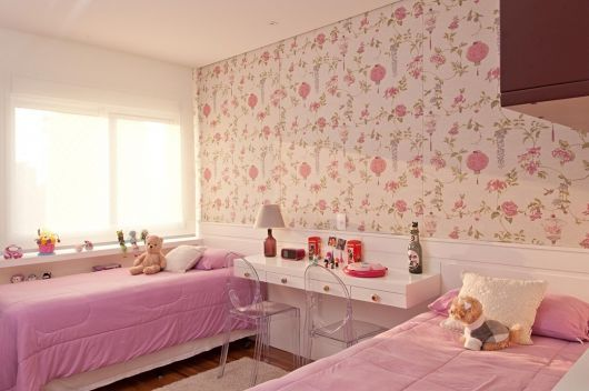 Quarto feminino infantil cor de rosa claro com papel de parede branco, rosa e lilás.