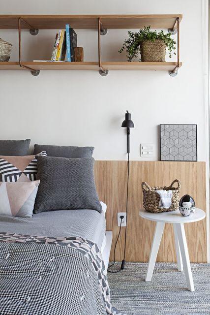 Quarto com decoração cinza e móveis de madeira.