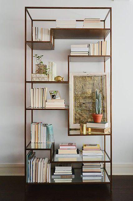 Estante metálica, com nichos irregulares e livros.