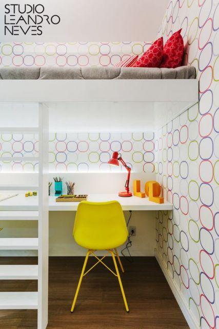 Beliche branco, parede com papel de parede e cadeira amarela na escrivaninha.