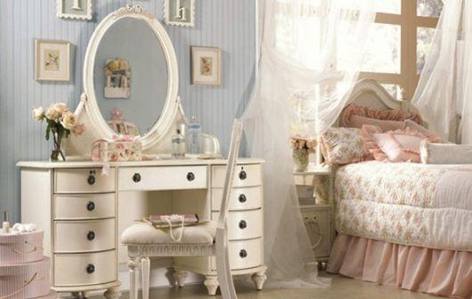 Modelo de quarto branco com cama de madeira branca e penteadeira branca.