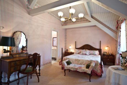 Modelo de quarto clean com cama de madeira rustica marrom, paredes rosa bebê e lustre.