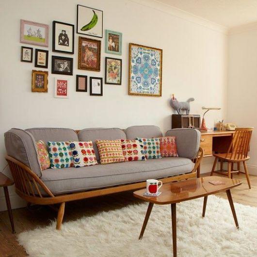 Modelo de sala com paredes claras, sofá com estofado cinza e mesinha de centro.