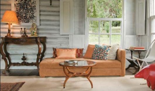 Sala com sofá na cor caramelo, com janela e paredes pintadas na cor cinza.