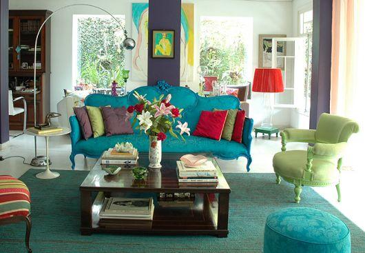 Sala decorada com almofadas coloridas e sofa na cor azul turquesa e mesinha de centro marrom.