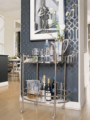 Modelo de carrinho de chá de vidro com metal prata em ambiente com paredes na cor cinza chumbo.