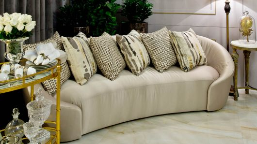 Modelo de carrinho de chá em tons dourados em uma sala com sofá grande em tons de bege.