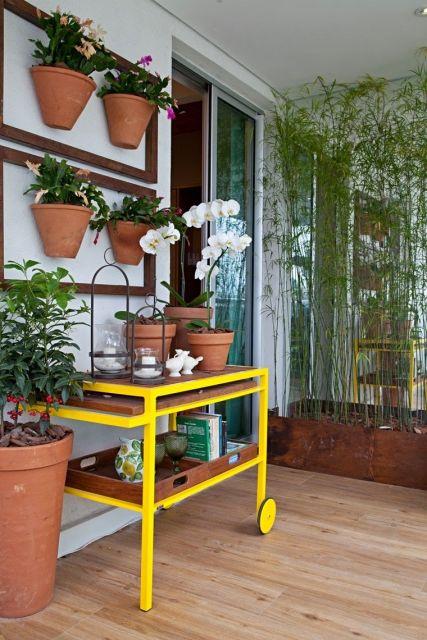 Modelo de carrinho em tons amarelo em varanda com plantas.