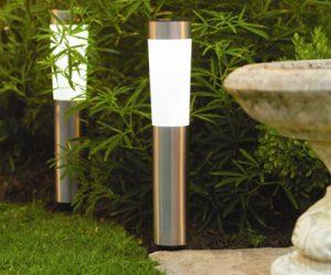 Duas luminárias solares instaladas no chão de um jardim próximas a uma parede com muitas folhas.