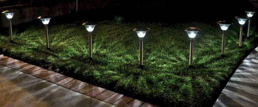Diversas luminárias solares posicionadas uma ao lado da outra em um jardim durante a noite.