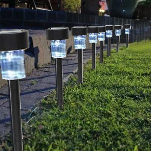 Oito luminárias solares acesas uma ao lado da outra iluminando o caminho de um corredor em um jardim.