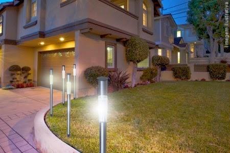 Cinco luminárias solares posicionadas uma ao lao da outra iluminando a entrada do jardim de uma casa grande.