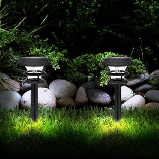 Duas luminárias solares lado a lado em um jardim com grama, árvores e pedras de decoração.