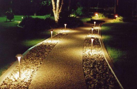 Caminho de um jardim composto por luminárias solares que estão acesas durante a noite.