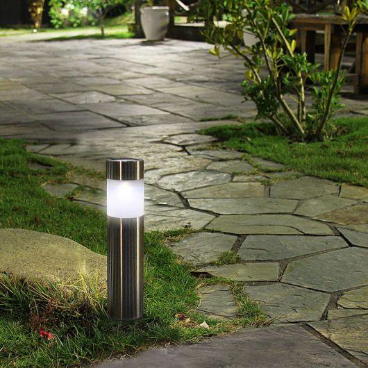 Uma luminária solar instalada em um jardim perto de uma pedra.