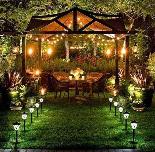 Espaço muito iluminado de um jardim com uma mesa e quatro cadeira. Existem diversas luminárias solares que iluminam o caminho até esse espaço.