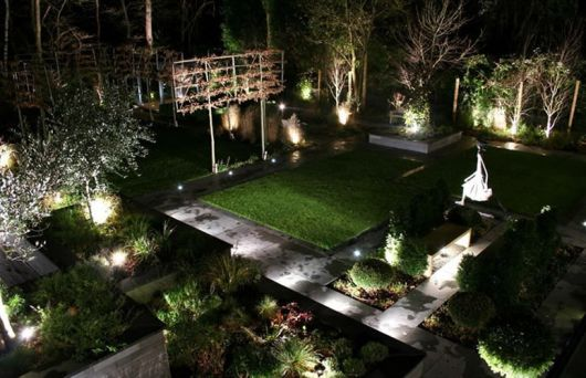 Foto mostrando um jardim inteiro composto por diversas plantas muito bem iluminadas com luminárias solares.