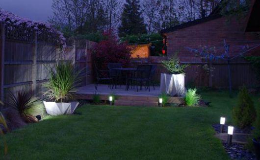 Jardim espaçoso com algumas luminárias solares pequenas posicionadas nos cantos para iluminação.