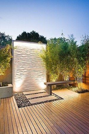 Parede alta em um jardim com muitos objetos de madeira iluminada por luminárias solares.