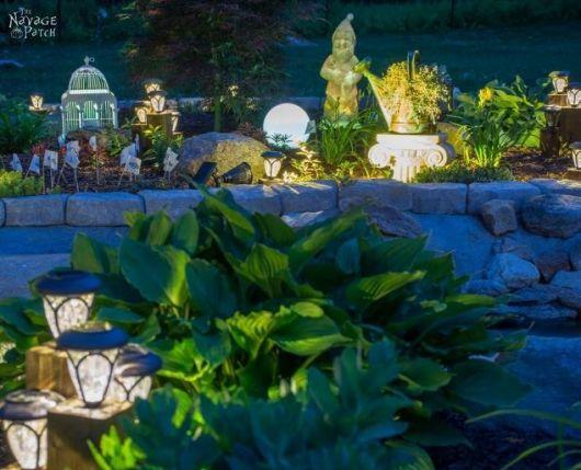 Jardim com muitos objetos de decoração iluminados por pequenas luminárias solares.