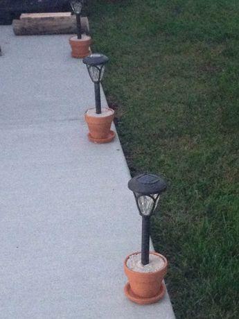 Luminárias solares em um jardim instaladas dentro de pequenos vasos.