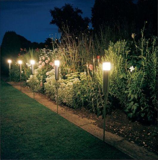 luminárias solares instaladas no chão de um jardim com uma altura considerável.