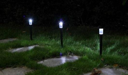 Três luminárias solares instaladas no jardim acesas durante a noite, uma do lado da outra.