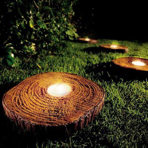 Luminárias solares instaladas dentro de tocos de tronco em um jardim próximas umas da outras.