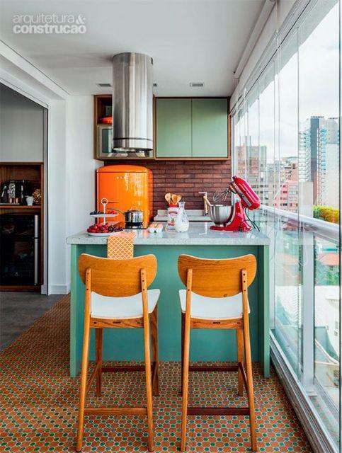 Foto de uma varanda gourmet pequena com parede de tijolinhos e uma bancada no centro com duas cadeiras.