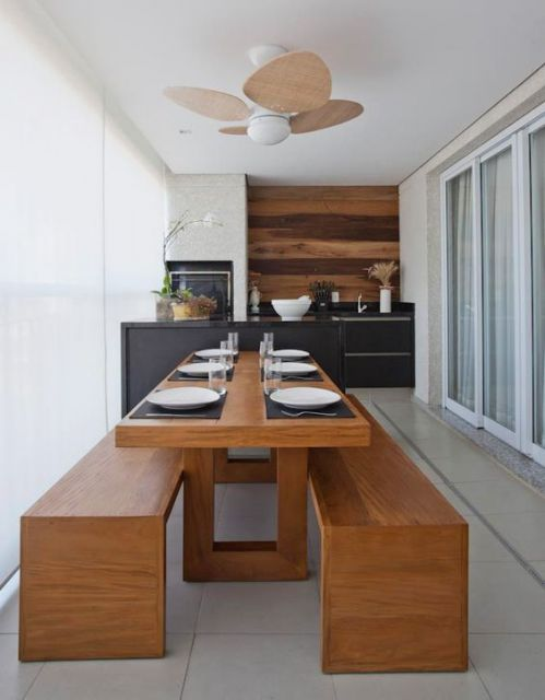 Foto de varanda gourmet espaçosa com uma mesa de jantar grande no centro com a louça disposta nela e uma pequena bancada ao fundo.